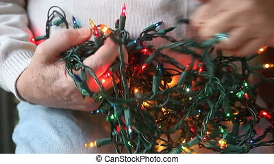 tangle of Christmas lights - a man tries to untangle a mess...