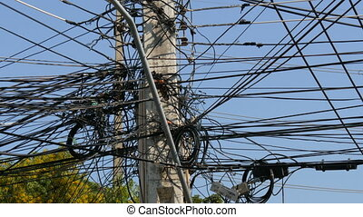 Tangled bundles of overhead wires. Electricity system on...