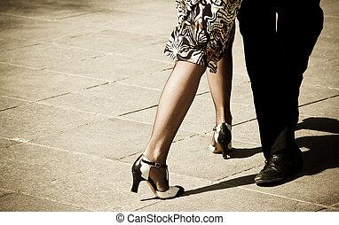 Street dancers performing tango dance. Aged warm tone.