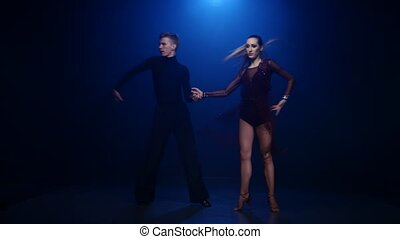 Tango dancing couple of professional elegant dancers on blue...