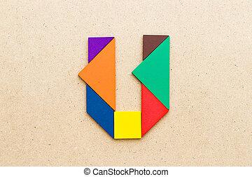 Tangram puzzle in alphabet letter U shape on wood background