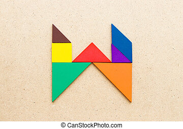 Tangram puzzle in alphabet letter W shape on wood background