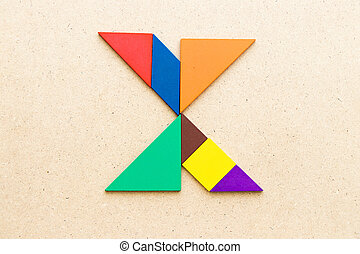 Tangram puzzle in alphabet letter X shape on wood background