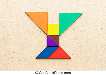 Tangram puzzle in alphabet letter Y shape on wood background