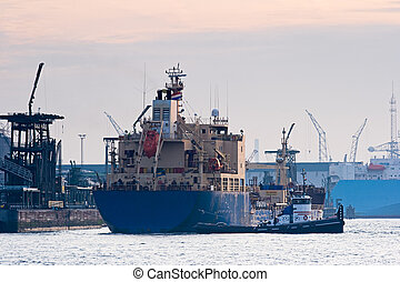 Tanker in harbor with tug