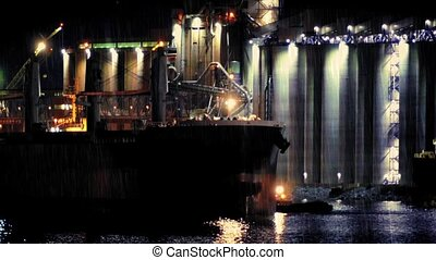 Tanker Passing Refinery At Night - Tug guides large tanker...