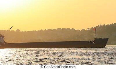 Tanker ship cruising against sunset