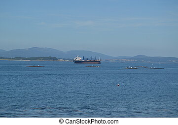 Tanker Ship Navigating The Estuary In Front Of The Horse Point Lighthouse On Arosa Island. Nature, Architecture, History, Travel. August 18, 2014. Isla De Arosa, Pontevedra, Galicia, Spain.