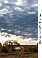 Tanker truck on the road leading through the countryside, in the background dramatic clouds and sunset.