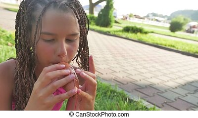 tanned girl is playing on ancient pipe. Musical instrument made of clay pipe