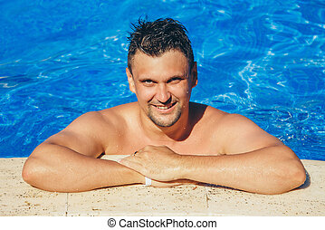 tanned man on vacation swimming in the pool
