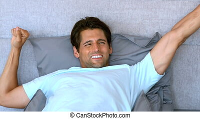 Tanned man waking up and stretching in his bed in slow...