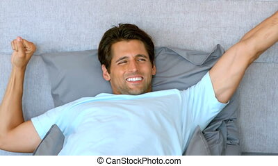 Tanned man waking up and stretching in his bed