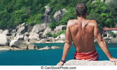 Tanned travler men relax on stone in front of Tanote Bay on...