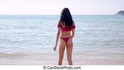 Tanned woman in sexy swimsuit walking on seaside