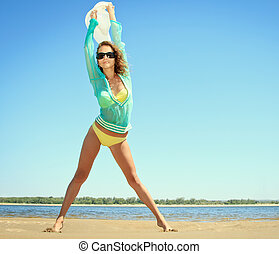 Tanned woman posing at the beach on summer day