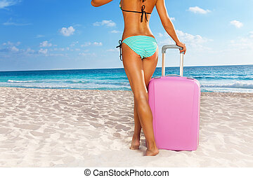Tanned woman standing with suitcase - Tanned woman standing ...