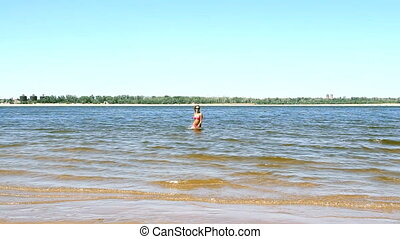 tanned young woman running out of the ocean