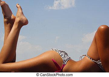 Tanning - Girl in bikini tanning in the bright summer sun.