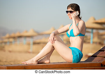 Tanning woman talking on mobile phone