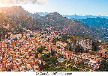 Taormina is a city on the island of Sicily, Italy. Aerial view from above in the evening at sunset light.