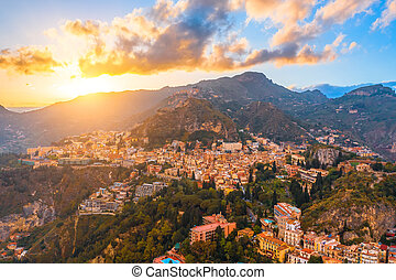 Taormina is a city on the island of Sicily, Italy. Aerial view from above in the evening at sunset.