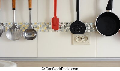 Tap is pouring water and kitchen utensils hang on the...