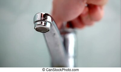 Tap water - Man\'s hand starting and stopping tap water in...