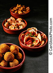 Tapas and seafood dishes over black