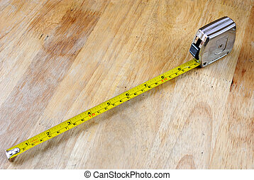 Tape Measurer on Wood - A tape measurer extended on a wooden...