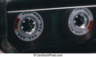 Tape Recorder Plays Transparent Audio Cassette. Close-up. Vintage audio cassette rotates in tape with a blank label used for sound recording in a retro cassette player. Call recording. Macro. 4K, 10 bit.