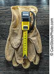 Tapeline safety gloves on wooden board.