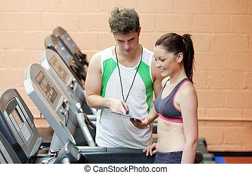 tapis roulant, debout, centre, entraîneur, femme, athlète, donner instruction, fitness, sérieux