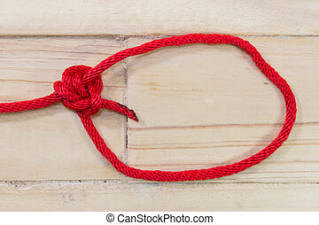 tarbuck knot made with red rope on wooden background.