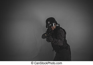 target, airsoft player with gun, helmet and bulletproof vest on gray background