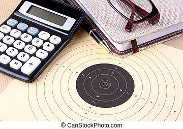 Target, calculator, pen, notebook, glasses - setting goals