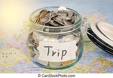 "Target for travel - concept saving money in a glass and word ""trip"" on map"