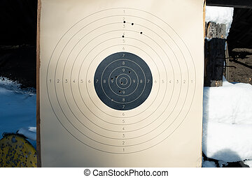 Target with numbers for shooting at a shooting range. A round target with a marked bull's-eye for shooting practice on the shooting range. Target with bullet holes.