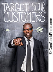 Target your customers! Confident young African man in formalwear pointing you while standing against blackboard with sketch on it