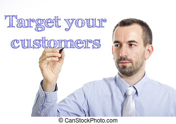 Target your customers - Young businessman writing blue text on transparent surface