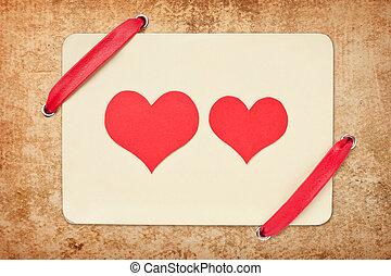 tarjeta de valentine, con, cinta roja, en, grunge, papel, fondo., dos, rojo, corazones, -, símbolo del amor