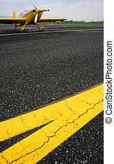 Tarmac - Yellow lines on the tarmac with aerobatics plane in...