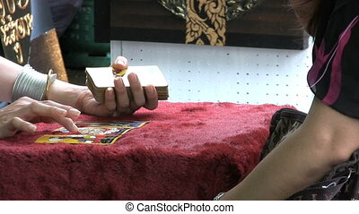 Tarot Card Reading Session - A tarot card reader tells a...