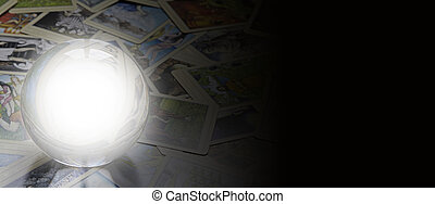 Wide website banner with blank crystal ball, scattered soft focus tarot cards and black background