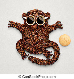 A funny tarsier made of roasted coffee beans, two cups and star anise with an oatmeal cookie.