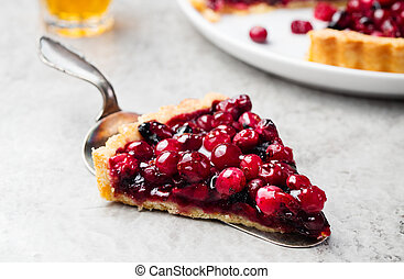 Tart, pie, cake with jellied fresh cranberries, bilberries and winter spices on a grey stone background