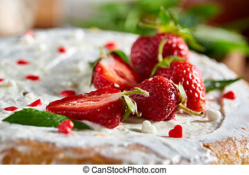 Tart with strawberries and whipped cream decorated with mint leaves on rustic wooden background, selective focus