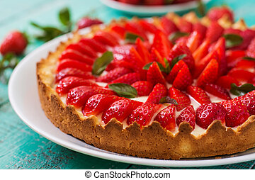 Tart with strawberries and whipped cream decorated with mint...