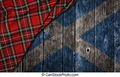 tartan textile on wooden background with scotland flag