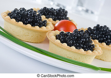 Tartlet with black caviar on a white platter, decorated with...